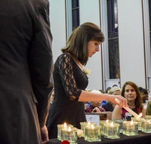 Elizabeth Hughes, granddaughter of four survivors, lights a candle in memory of children who perished.