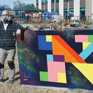 Hillel Smith with his mural for the ViBe District.