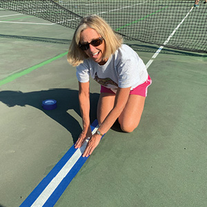 Stephanie Calliot helps prepare courts for pickleball.